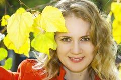 Giovane bella ragazza bionda con i fogli gialli Immagine Stock