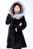 Giovane bella ragazza bionda in una pelliccia nera Immagine Stock