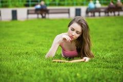 Giovane bella ragazza castana che legge un libro all'aperto Fotografie Stock Libere da Diritti