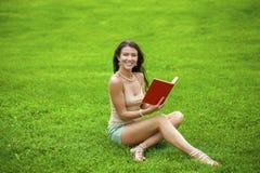 Giovane bella ragazza castana che legge un libro all'aperto Fotografie Stock