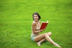 Giovane bella ragazza castana che legge un libro all'aperto Fotografia Stock Libera da Diritti