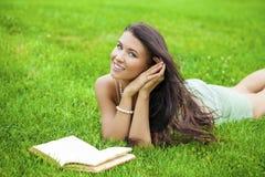 Giovane bella ragazza castana che legge un libro all'aperto Fotografia Stock