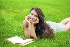 Giovane bella ragazza castana che legge un libro all'aperto Immagine Stock Libera da Diritti