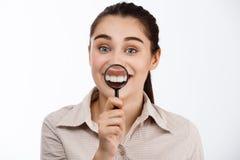 Giovane bella ragazza castana sorridente che esamina macchina fotografica che mostra i denti tramite la lente sopra fondo bianco Immagini Stock
