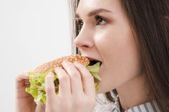 Giovane bella ragazza castana su un fondo bianco con un hamburger in sue mani Mangiando con gli alimenti a rapida preparazione di immagine stock libera da diritti