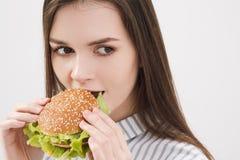 Giovane bella ragazza castana su un fondo bianco con un hamburger in sue mani Mangiando con gli alimenti a rapida preparazione di fotografia stock