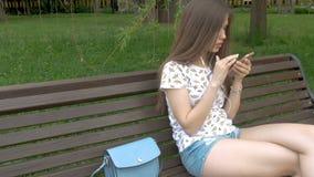 Giovane bella ragazza che ascolta la musica tramite le cuffie archivi video