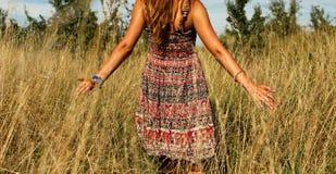 Giovane bella ragazza che cammina nel campo e nella mano di funzionamenti attraverso l'alta erba asciutta all'estate Immagine Stock