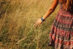 Giovane bella ragazza che cammina nel campo e nella mano di funzionamenti attraverso l'alta erba asciutta all'estate Fotografie Stock Libere da Diritti