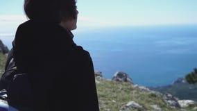 Giovane bella ragazza che cammina sopra la montagna sopra il mare video d archivio