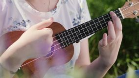 Giovane bella ragazza che gioca la chitarra delle ukulele video d archivio