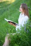 Giovane bella ragazza che guarda meditatamente nel cielo, sedentesi Immagine Stock Libera da Diritti
