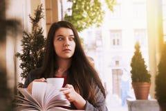 Giovane bella ragazza che legge un'istruzione del libro all'aperto, auto de Fotografie Stock Libere da Diritti