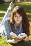 Giovane bella ragazza che legge un libro all'aperto Immagine Stock
