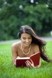 Giovane bella ragazza che legge un libro esterno Immagine Stock Libera da Diritti