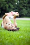 Giovane bella ragazza che legge un libro esterno Immagine Stock