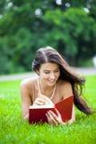 Giovane bella ragazza che legge un libro esterno Fotografie Stock