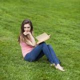 Giovane bella ragazza che legge un libro esterno Fotografia Stock