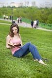 Giovane bella ragazza che legge un libro esterno Immagini Stock Libere da Diritti