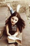 Giovane bella ragazza che legge un libro sulle scale nel vecchio rimorchio Immagine Stock Libera da Diritti