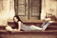 Giovane bella ragazza che legge un libro sulle scale in un vecchio euro Fotografie Stock
