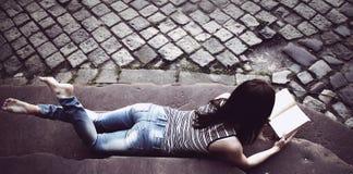 Giovane bella ragazza che legge un libro sulle scale in un vecchio euro Fotografia Stock Libera da Diritti