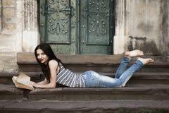 Giovane bella ragazza che legge un libro sulle scale in un vecchio euro Immagini Stock Libere da Diritti
