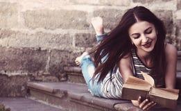 Giovane bella ragazza che legge un libro in un vecchio edu europeo della città Fotografie Stock