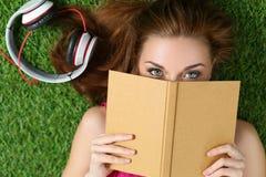 Giovane bella ragazza che mette sull'erba in parco che tiene un libro Fotografie Stock Libere da Diritti