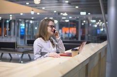 Giovane, bella ragazza che parlano sul telefono che sta ad una tavola con un computer portatile e una tazza di caffè all'aeroport Fotografie Stock Libere da Diritti