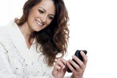 Giovane bella ragazza che per mezzo dello Smart Phone Fotografie Stock Libere da Diritti