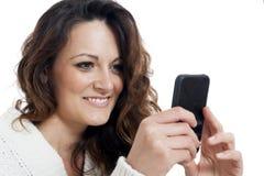 Giovane bella ragazza che per mezzo dello Smart Phone Fotografia Stock