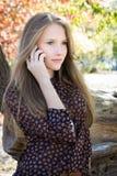 Giovane bella ragazza che rivolge al telefono cellulare in parco Fotografia Stock Libera da Diritti