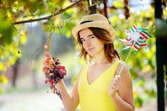 Giovane bella ragazza che seleziona uva piena nel giorno soleggiato in Italia Fotografia Stock