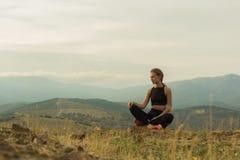 Giovane bella ragazza che si siede in montagne fotografia stock libera da diritti
