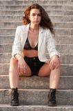Giovane bella ragazza che si siede su alcuni punti fuori Ragazza in pantaloncini corti in jeans del reggiseno e rivestimento bian immagine stock