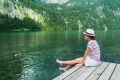 Giovane bella ragazza che si siede su un pilastro dal lago Konigssee con chiara acqua verde Fotografia Stock