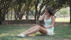 Giovane bella ragazza che si siede sul prato inglese in parco facendo uso del PC della compressa, concetto online di acquisto stock footage