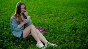 Giovane bella ragazza che si siede sull'erba e sulle manifestazioni nel telefono stock footage