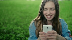 Giovane bella ragazza che si siede sull'erba e sulle manifestazioni nel telefono video d archivio
