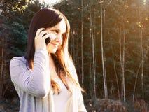 Giovane bella ragazza che sorride e che parla sul telefono nella foresta al tramonto fotografia stock