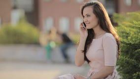 Giovane bella ragazza con capelli lunghi nella città che parla su un telefono cellulare stock footage