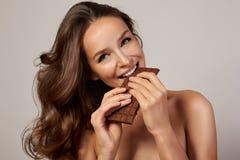 Giovane bella ragazza con capelli ricci scuri, le spalle nude ed il collo, tenenti una barra di cioccolato per godere del gusto e Fotografia Stock Libera da Diritti