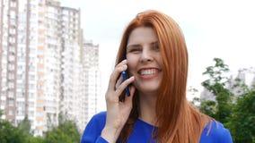 Giovane bella ragazza con capelli rossi nella città, quadranti un il numero di telefono, parlante su un telefono cellulare e su u stock footage