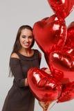 Giovane bella ragazza con gli aerostati rossi su un fondo grigio 8 marzo concetto Fotografia Stock