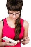 Giovane bella ragazza con i vetri che legge un libro. isolato Fotografie Stock