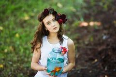 Giovane bella ragazza con il pesce dell'oro Fotografia Stock