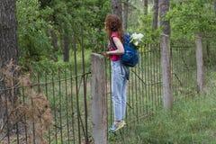 Giovane bella ragazza con lo zaino che scavalca il recinto Fotografie Stock Libere da Diritti