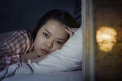 Giovane bella ragazza coreana asiatica che si trova sulla sensibilità di sofferenza premurosa sembrante sveglia a tarda notte di  immagini stock