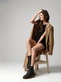 Giovane bella ragazza dei pantaloni a vita bassa che si siede sulla sedia che pensa in piccolo immagine stock